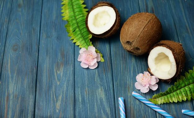 Baner egzotyczny owoc kokosowy w całości i na pół z liśćmi zielonymi