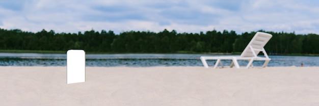 Baner, makieta smartfona w piasku na plaży. na tle leżaka, wody i drzew. koncepcja na temat podróży.