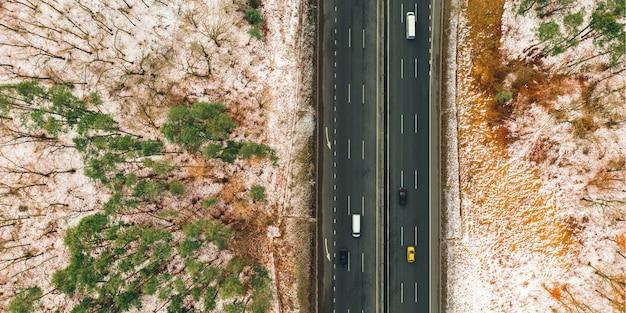 Baner motywu transportowego: fragment autostrady z samochodami z widokiem na zaśnieżony las