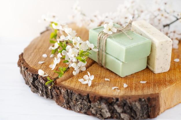Baner mydlany. aromatyczne mydło naturalne z kwiatami sakura na drewnianym tle, zbliżenie