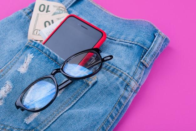 Baner na różowej powierzchni z niebieskimi dżinsami, pieniędzmi, słuchawkami, telefonem, okularami.