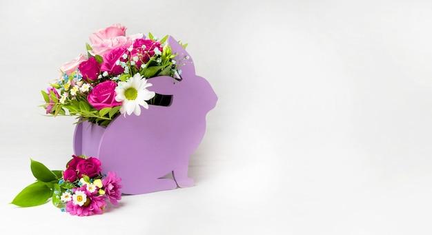 Baner na stronę florystyczną doniczki w postaci królika z kompozycją kwiatową na białym tle