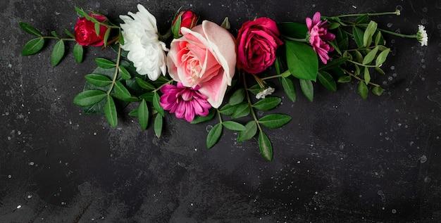 Baner na stronę internetową z kompozycją delikatnych letnich kwiatów na czarnym tle widok z góry za darmo