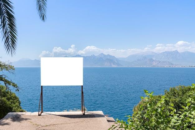 Baner nad brzegiem morza. pusta makieta jest obiektem do ogłoszeń o wakacjach, wycieczkach morskich czy rejsach morskich.