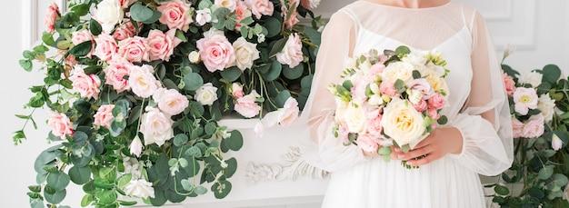 Baner ślubny. panna młoda z bukietem w dłoniach na tle kwiatów.