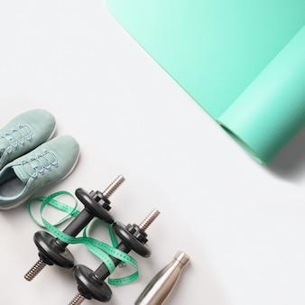 Baner sprzętu sportowego i fitness, mata do jogi, buty, butelka wody na szaro. widok z góry, miejsce na