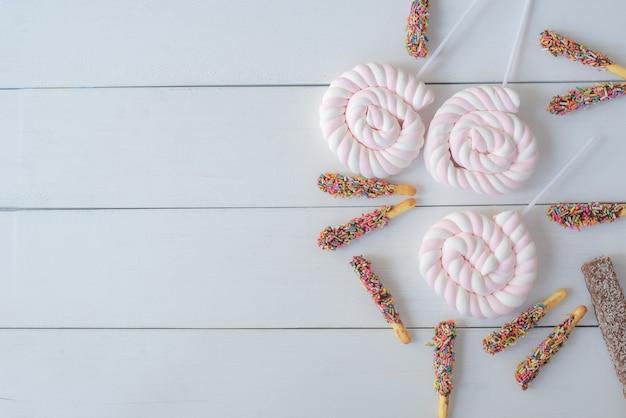 Baner walentynkowy z bocznym obramowaniem różnych słodyczy i ciasteczek widok z góry nad białym drewnem