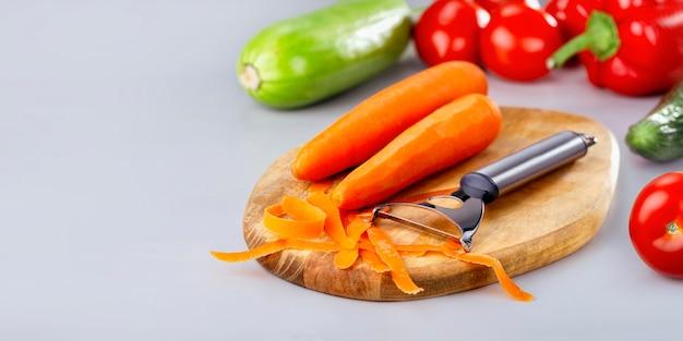 Baner warzyw. gotowanie i jedzenie warzyw. obieranie surowej marchewki i różnych warzyw na desce.