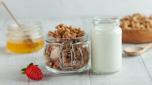 Baner z domowym mlekiem granola w słoiku z miodem i truskawkami na drewnianym tle koncepcja...