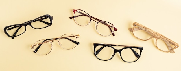 Baner z kolekcją okularów na pastelowej ścianie. sklep optyczny, dobór okularów, badanie wzroku, badanie wzroku u optyka, koncepcja akcesoriów modowych. widok z góry, płaski układ