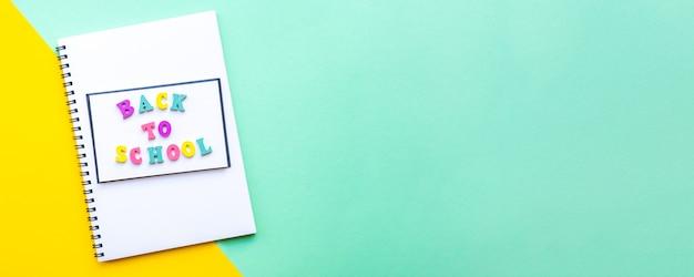 Baner z notatnikiem na spirali z białymi kartkami powrót do szkoły z wielokolorowym napisem