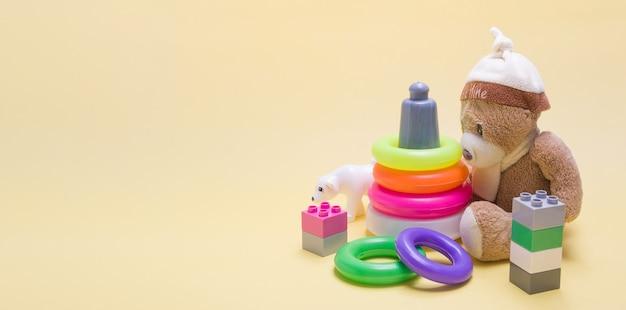 Baner z zabawkami dla dzieci i miejscem na kopię. miś p, piramida i konstruktor na żółtym tle