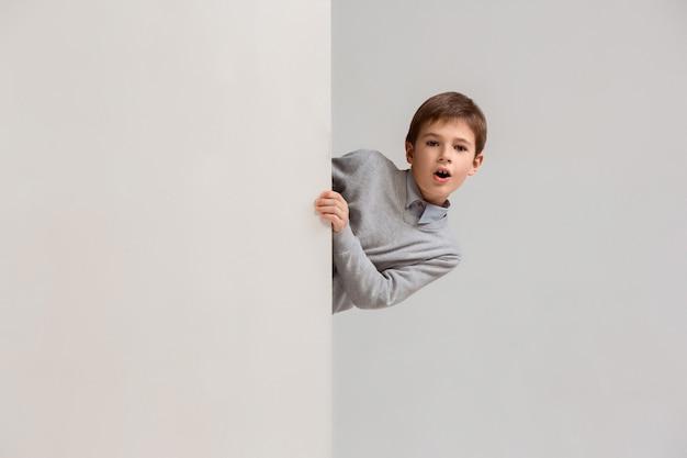 Baner z zaskoczonym dzieckiem zaglądającym na brzeg
