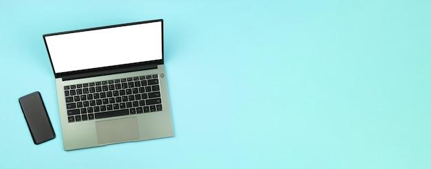 Baner ze smartfonem i białą makietą na ekranie laptopa na niebieskim tle widok z góry