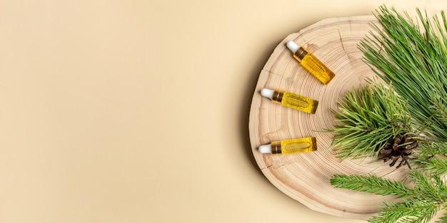 Baner ze zdrowymi iglastymi olejkami aromatycznymi spa. trzy małe szklane butelki z iglastymi olejkami eterycznymi z sosny, świerka i cedru z ich gałęziami na drewnianym cięciu na beżu z kopią przestrzeni. widok z góry.