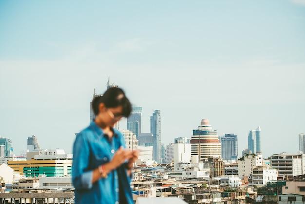 Bangkok pejzażu miejskiego scena z rozmytą kobietą używał mądrze telefon w przedpolu z kopii przestrzenią