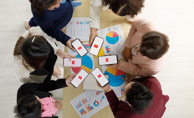 Bangkok/tajlandia – 06 sierpnia 2021: ludzie trzymają smartfony różnych marek i różnych systemów operacyjnych z logo youtube, najpopularniejszym portalem wideo na świecie.