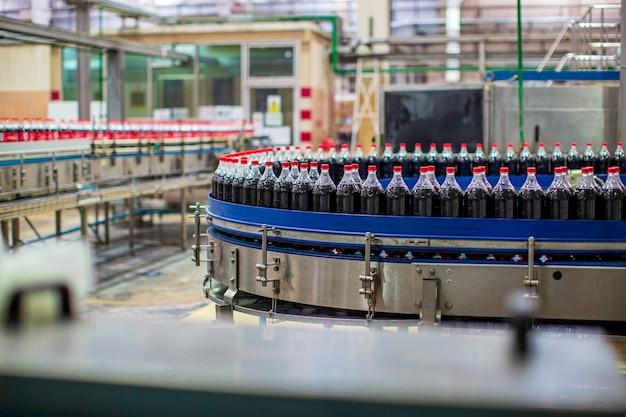 Bangkok tajlandia - 10 czerwca 2020 r. wnętrze fabryki napojów. przenośnik przepływający z butelkami na wodę gazowaną.