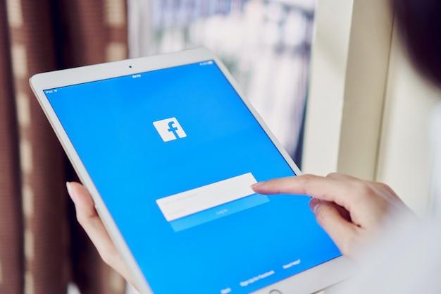 Bangkok, tajlandia - 11 czerwca 2018: ręka naciska przycisk facebook na apple ipad pro
