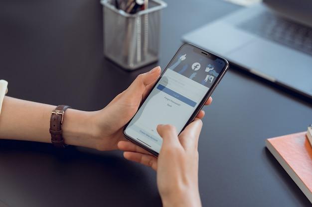 Bangkok, tajlandia - 11 maja 2020: ręka trzyma smartfon i ekran facebooka na telefonie, media społecznościowe używają do wymiany informacji i sieci.