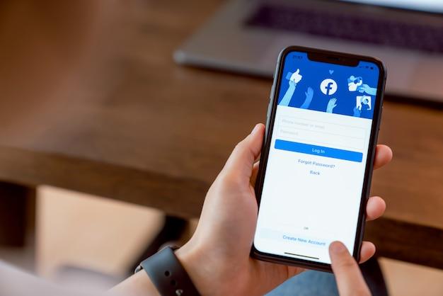 Bangkok, tajlandia - 17 lutego 2020: ręka kobiety naciska ekran facebooka na apple iphone, media społecznościowe używają do wymiany informacji i sieci.