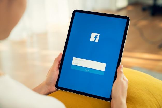 Bangkok, tajlandia - 30 kwietnia 2020: kobiety ręka trzyma cyfrowy tablet i naciskając ekran facebooka na apple ipad, media społecznościowe używają do wymiany informacji i sieci.