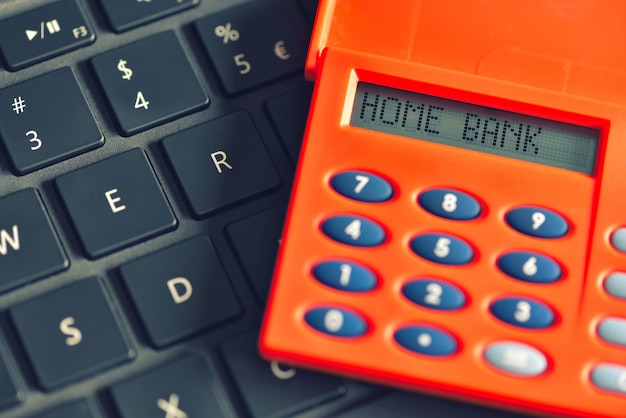 Bank domowy napisany na wyświetlaczu cyfry nad klawiaturą komputera. koncepcja transakcji bankowości internetowej