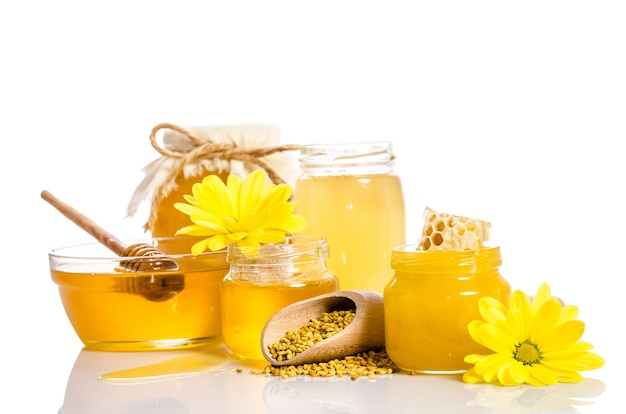 Bank miodu z plastrami miodu, szklana miska z miodem i drewniana miarka z pyłkiem