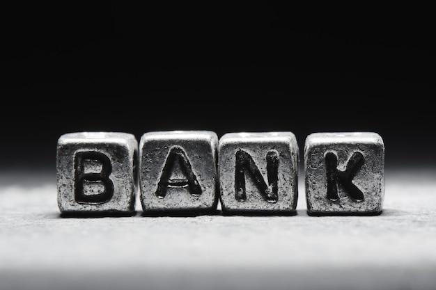 Bank napis na metalowych kostkach w stylu grunge na czarnym tle na białym tle