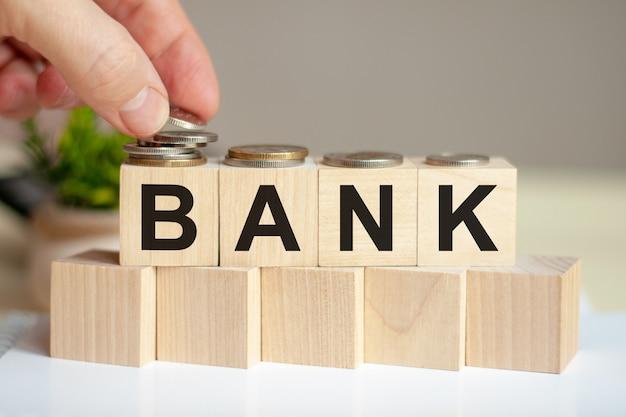 Bank słowo napisane na drewnianych kostkach. ręka mężczyzny umieszcza monety na powierzchni sześcianu. zielona roślina doniczkowa na tle. koncepcja biznesu i finansów.