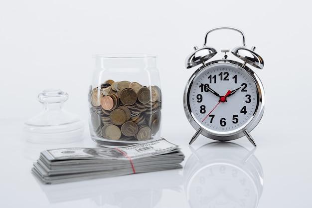 Bank z monetami, banknotami dolarowymi i budzikiem. czas to pieniądz.