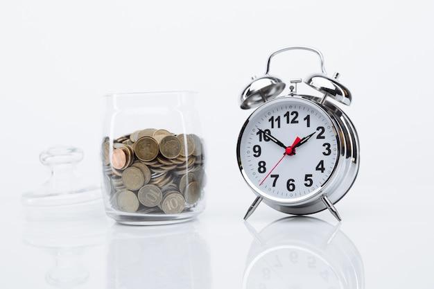 Bank z monetami i budzikiem na szklanym stole