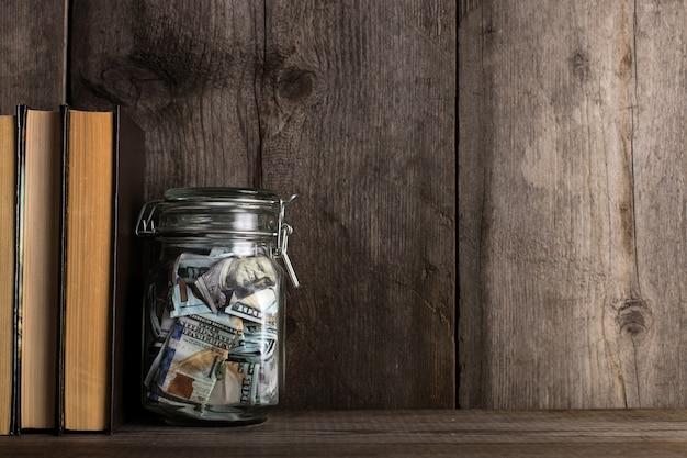 Bank z pieniędzmi na starym drewnianym półce.