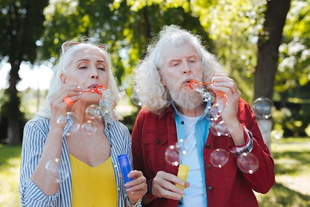 Bańki mydlane. przyjemni starsi ludzie dmuchają bańki mydlane podczas wspólnej zabawy
