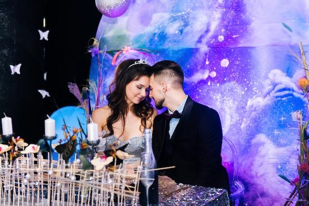 Bankiet w hali. prezydium w stylu kosmosu. uroczystość. ustawienie stołu panna młoda i pan młody dzień ślubu. siedzi przy stole.