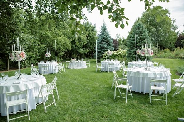 Bankiet weselny w plenerze, wystrój weselny na stołach gości