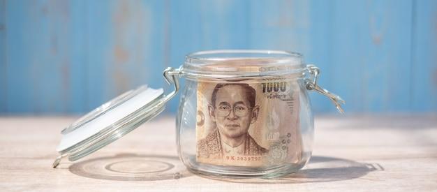 Banknot 1000 bahtów tajskich w szklanym słoju. pieniądze, biznes, inwestycje