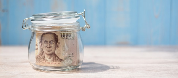 Banknot 1000 bahtów tajskich w szklanym słoju. pieniądze, biznes