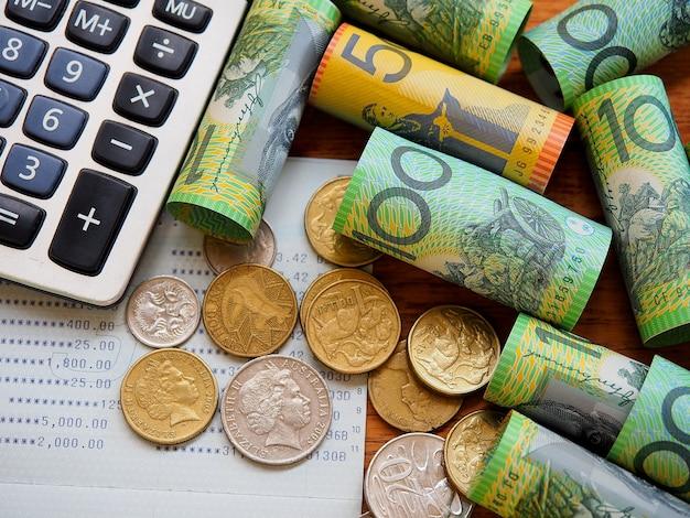 Banknot australijski, monety, księga rachunkowa i kalkulator w widoku z góry