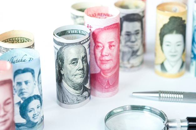 Banknot dolara amerykańskiego i juana wśród międzynarodowych banknotów. jest symbolem kryzysu wojny taryfowej między stanami zjednoczonymi ameryki a chinami, które są największym krajem gospodarczym na świecie.