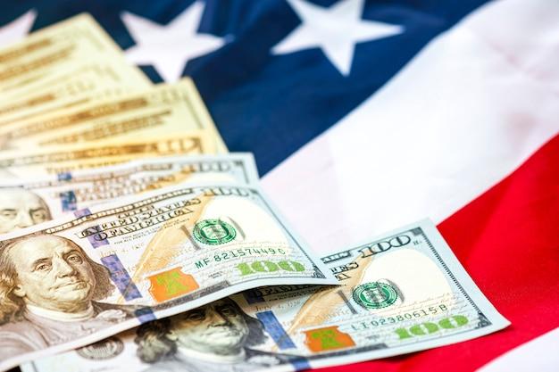 Banknot dolara amerykańskiego na fladze usa. dolar amerykański jest główną i popularną walutą wymiany na świecie. koncepcja inwestycji i oszczędności.