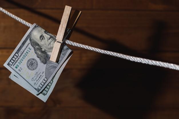 Banknot dolara amerykańskiego zawieszony jest na sznurku ze spinaczem do bielizny. pojęcie prania pieniędzy.