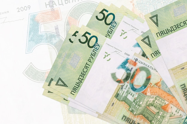 Banknoty 50 rubli białoruskich leżą w stosie na ścianie dużego półprzezroczystego banknotu. streszczenie prezentacji waluty krajowej. pomysł na biznes