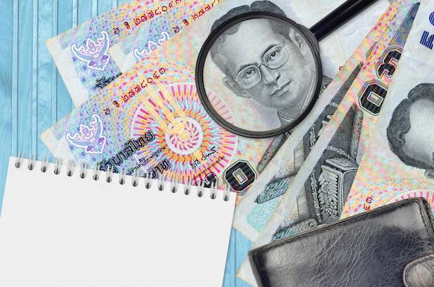 Banknoty 50 tajlandzkich bahtów i szkło powiększające, czarna torebka i notatnik