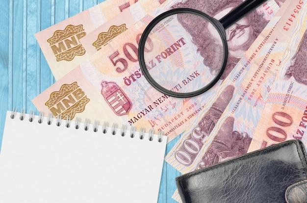 Banknoty 500 forintów węgierskich i szkło powiększające z czarnym portfelem