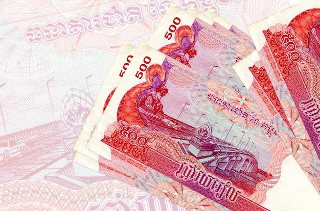 Banknoty 500 rielów kambodżańskich leżą na stosie na ścianie dużego półprzezroczystego banknotu. streszczenie prezentacji waluty krajowej. pomysł na biznes