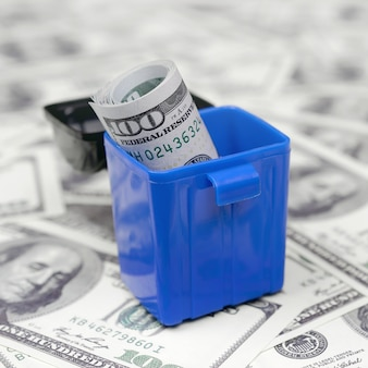 Banknoty amerykańskie wrzucane są do kosza na śmieci na setkach banknotów dolarowych