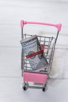 Banknoty dolara amerykańskiego w rolce w koszyku