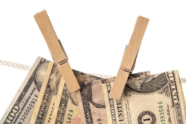 Banknoty dolara amerykańskiego zawieszone są na sznurku za pomocą spinaczy do bielizny. pojęcie prania pieniędzy.
