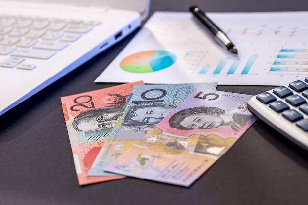 Banknoty dolara australijskiego, laptop i schemat na czarnym stole